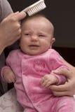 Moeder die babyhaar kamt royalty-vrije stock afbeelding