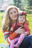 Moeder die babymeisje in de lentegazon koesteren Stock Foto