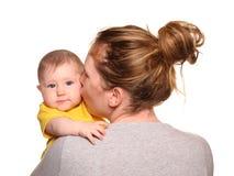 Moeder die babymeisje een kus op de wang geven royalty-vrije stock afbeelding