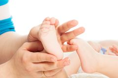 Moeder die babyvoeten masseren Stock Foto
