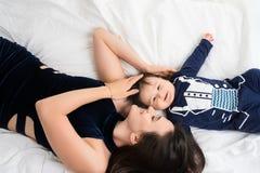Moeder die in bed met hoog de hoekschot van de babyjongen liggen stock afbeelding
