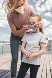 moeder die beschermend masker op dochter voor de ademhaling van lucht dragen stock foto