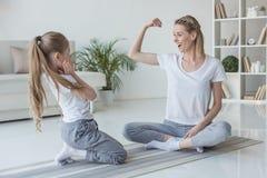moeder die bicepsenspier tonen aan haar dochter royalty-vrije stock afbeelding