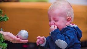 Moeder die de bal geven aan schreeuwende baby stock videobeelden