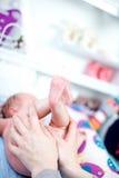 Moeder die de bodem van haar baby houden Stock Foto's