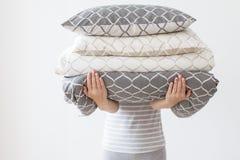 Moeder die de moderne beige en grijze stapel van het bedlinnen, het bed van de kinderenruimte houden stock fotografie