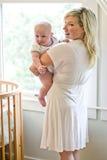 Moeder die de oude baby van zeven maanden naast voederbak vervoert Royalty-vrije Stock Afbeelding
