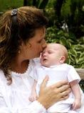 Moeder die de Pasgeboren Jongen van de Baby van de Slaap kust stock foto