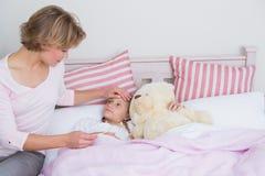 Moeder die de temperatuur van zieke dochter vergen Stock Afbeeldingen