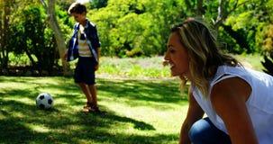 Moeder die de van de picknickdeken en zoon speelvoetbal in park 4k uitspreiden stock videobeelden