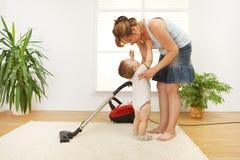 Moeder die de vloer schoonmaakt Stock Afbeelding