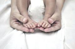 Moeder die de voeten van haar Baby houdt Stock Foto's