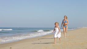 Moeder die Dochter langs Strand achtervolgen stock video