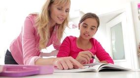 Moeder die dochter met thuiswerk helpen stock video