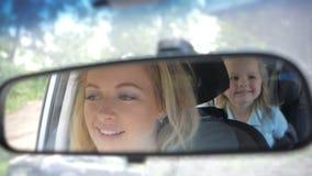 Moeder die een auto drijven, die haar hebben weinig babymeisje in een kindzetel stock footage