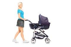 Moeder die een babywandelwagen duwt Stock Foto
