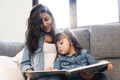 Moeder die een boek lezen aan haar dochter royalty-vrije stock fotografie