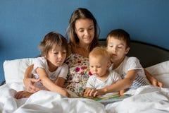 Moeder, die een boek lezen aan haar kinderen in de ochtend in bed stock afbeeldingen