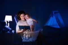 Moeder die een boek lezen aan weinig baby Stock Afbeelding