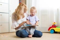 Moeder die een boek met haar zoon thuis bekijken stock fotografie