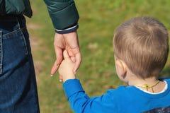 Moeder die een hand van zijn zoon in de zomerdag in openlucht houden stock afbeeldingen
