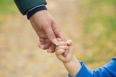 Moeder die een hand van zijn zoon in de zomerdag in openlucht houden stock foto