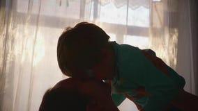 Moeder die een klein kind op zijn handen houden Zonstralen door het venster Het gelach en de vreugde van de baby stock videobeelden