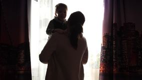 Moeder die een klein kind op zijn handen houden Zonstralen door het venster Het gelach en de vreugde van de baby stock video