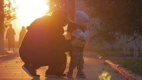 Moeder die een kleine zoon in een de herfstpark omcirkelen Gelukkige familie in de herfstpark Gelukkige familie in aardconcept in stock video