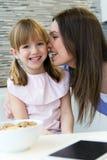 Moeder die een kus geven aan zijn dochter op de wang stock afbeeldingen