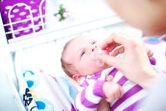 Moeder die een model in de mond van een baby zetten Royalty-vrije Stock Fotografie