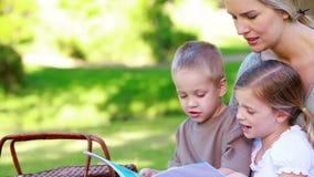 Moeder die een prentenboek met haar jonge kinderen kijken stock video