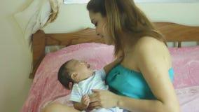 Moeder die een schreeuwende pasgeboren baby in haar slaapkamer troosten stock footage