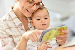 Moeder die een verhaal lezen aan haar baby stock afbeeldingen