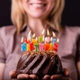 Moeder die een verjaardagscake met kleurrijke kaarsen houden Verjaardag, partij en familieconcept royalty-vrije stock foto