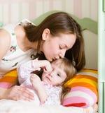 Moeder die een ziek kind kussen Stock Afbeelding
