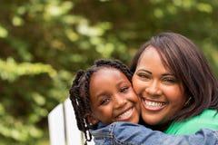 Moeder die en haar dochter glimlachen koesteren Stock Fotografie