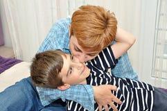 Moeder die en haar zoon koesteren kussen Stock Afbeelding