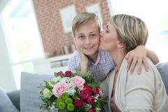 Moeder die en kus danken geven aan haar zoon stock foto