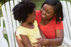Moeder die en met haar dochter glimlachen spreken Royalty-vrije Stock Foto's