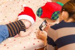 Moeder die foto die van zoon nemen Santa Claus-hoeden dragen Stock Foto