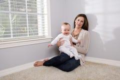 Moeder die gelukkige halfjaarlijkse oude baby houdt royalty-vrije stock fotografie