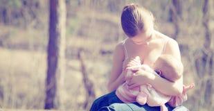 Moeder die haar baby in aard in openlucht in het park voeden Stock Afbeelding