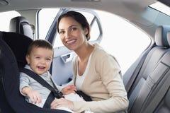 Moeder die haar baby in de autozetel beveiligen stock foto