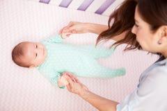 Moeder die haar baby in een voederbak bekijken stock foto