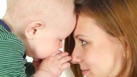 Moeder die haar baby kussen terwijl hij speelt wit Sluit omhoog stock video