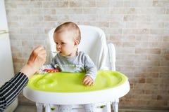 Moeder die haar baby met een lepel, kind voeden die in zonnige keuken eten De ruimte van het exemplaar stock foto's