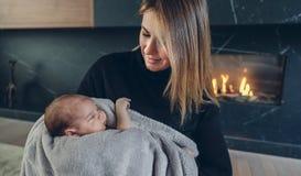 Moeder die haar baby voor open haard koesteren royalty-vrije stock afbeeldingen