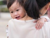 Moeder die haar baby in wapens vervoeren Stock Foto