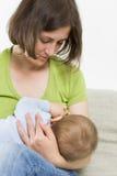 Moeder die haar babyjongen de borst geven. Stock Foto's